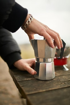 Uomo che fa il caffè da campeggio all'aperto con caffettiera geyser in metallo su un bruciatore a gas, passo dopo passo.