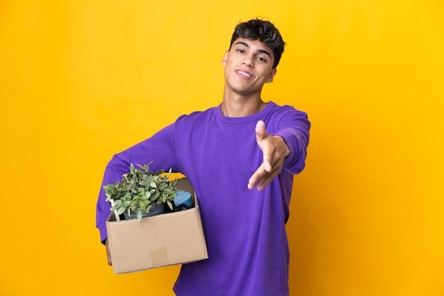 Uomo che fa una mossa mentre prende una scatola piena di cose che stringe la mano per chiudere un buon affare