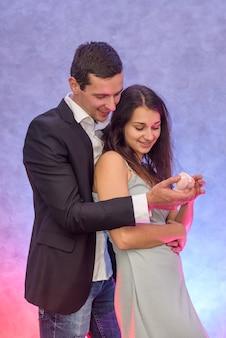 Uomo che fa una proposta alla sua ragazza mostrando il suo anello d'oro con diamante