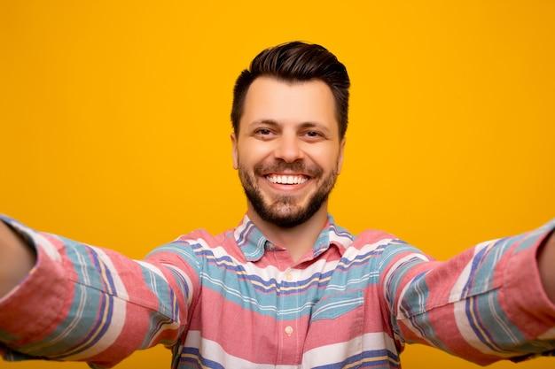 Uomo che fa selfie e in piedi su sfondo arancione.