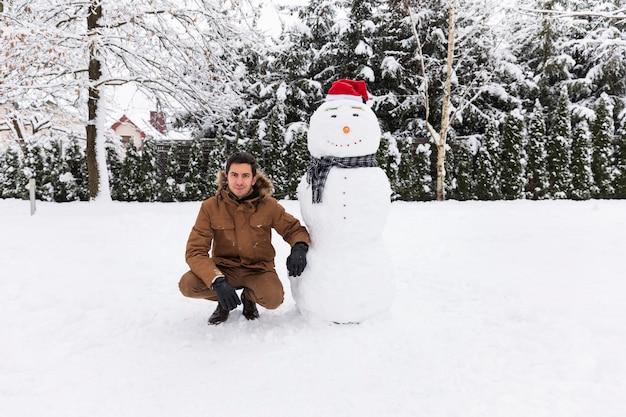 Uomo che fa un pupazzo di neve nel suo cortile.