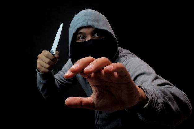 Uomo in maschera che tiene coltello nell'oscurità, crimine di violenza o illustrazione di rapina