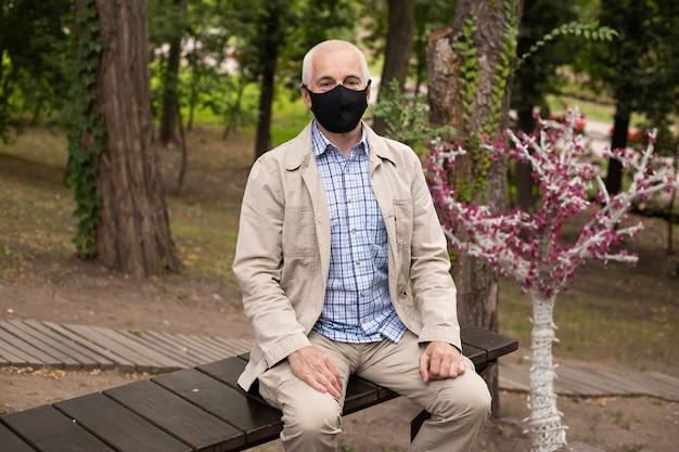 Uomo in maschera nel parco. protezione dalla malattia.
