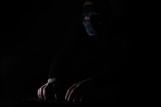 Un uomo con una maschera stampa sulla tastiera a un tavolo al buio