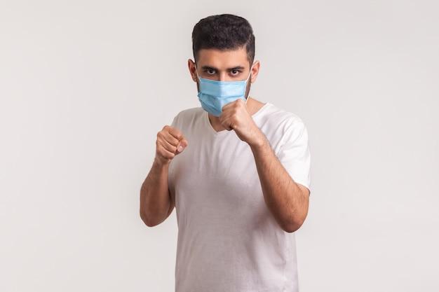 Uomo in maschera che punzona la boxe alla telecamera, combattendo contro malattie contagiose, infezione da coronavirus