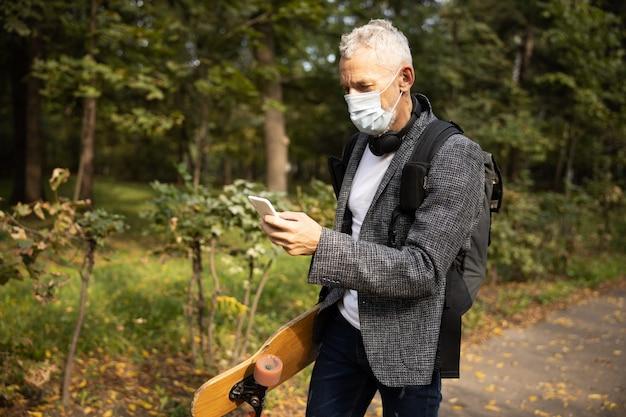 Uomo in maschera che utilizza smartphone in passeggiata