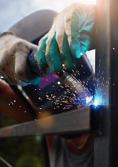 Un uomo mascherato salda una struttura in ferro con una macchina semiautomatica in campagna