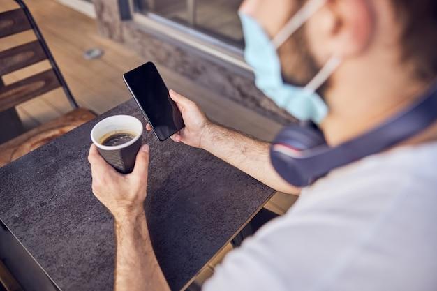 Uomo in maschera con una tazza di caffè che guarda nello smartphone