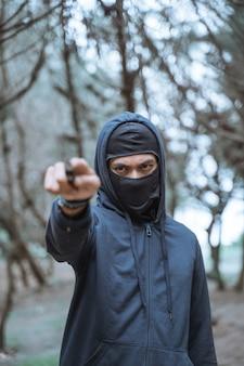 Uomo in una maschera con un coltello che indossa abiti neri su una foresta