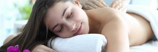 L'uomo fa il massaggio per la bella donna che giace a pancia in giù sul lettino da massaggio