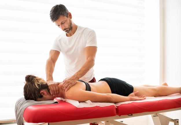 Uomo che massaggia il trapezio della donna