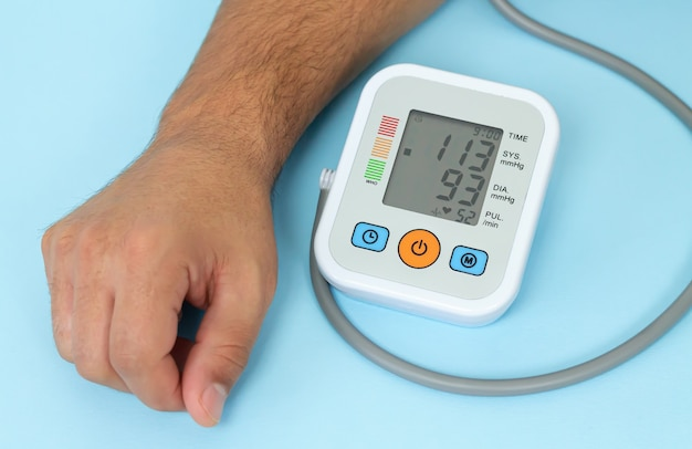 L'uomo misura la sua pressione sanguigna dal primo piano del tonometro elettronico