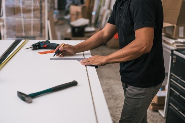 Uomo che misura una superficie con un quadrato in un'officina