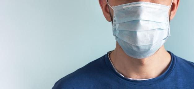 Uomo nella mascherina medica di protezione del viso sulla parete leggera. coronavirus ed epidemia