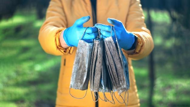Uomo in guanti medicali in possesso di un mazzo di maschere mediche sporche sollevate da terra