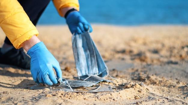 Uomo in guanti medicali raccogliendo un mucchio di maschere mediche sporche dalla spiaggia di un lago