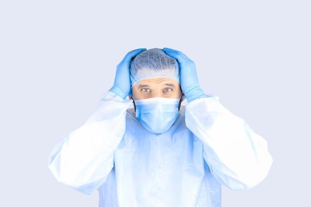 Uomo in abito medico, maschera e guanti che tengono la testa mostrando gesto di orrore