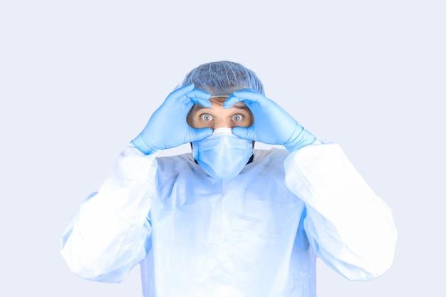 Un uomo in camice medico, maschera e guanti si portò le mani agli occhi e li guardò.