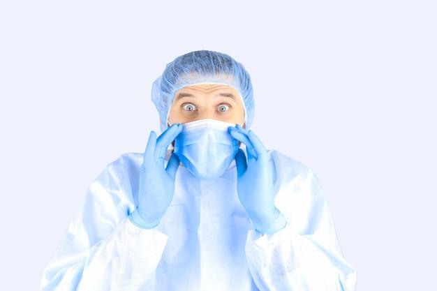 L'uomo in un camice medico, maschera e guanti mostra un gesto di sorpresa