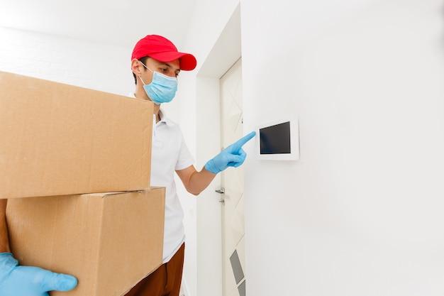 Un uomo una maschera medica e guanti di gomma blu con una scatola, un pacco tra le mani. consegna di cibo durante la quarantena della pandemia di coronavirus. consegna a domicilio, ordine online. acquisti online .