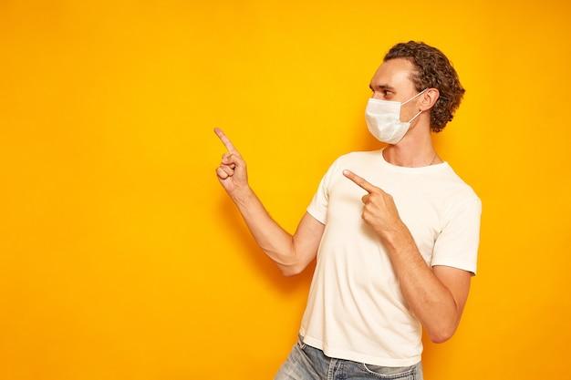 L'uomo con una maschera medica abbigliamento casual indica con le mani un'area vuota su uno sfondo giallo