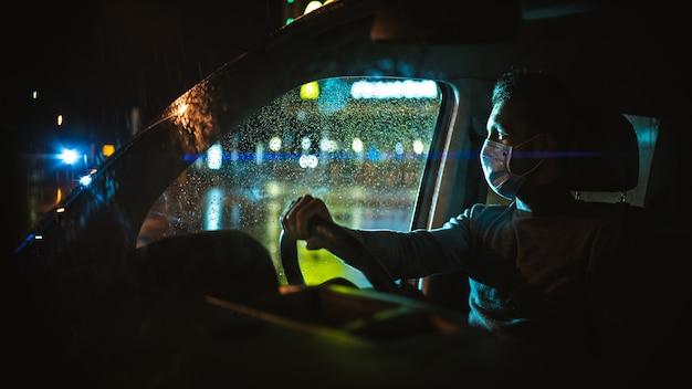 L'uomo in maschera medica che guida l'auto sulla strada piovosa notturna