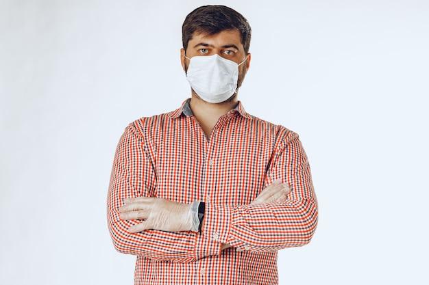 Uomo con la mascherina medica e guanti medicali per la protezione.