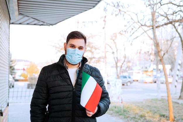 Uomo in mascherina medica, maschera protettiva con bandiera italiana