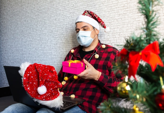Uomo in maschera medica che condivide i regali della scatola tramite videochiamate