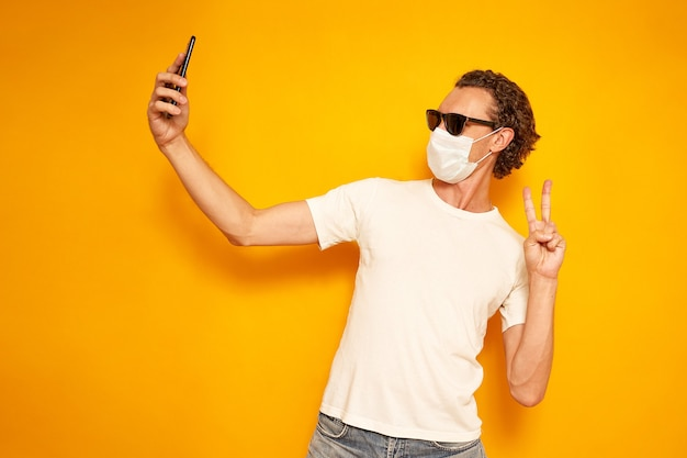 La maschera medica dell'uomo prende selfie fa i punti di videochiamata alla fotocamera dello smartphone si gode il tempo libero