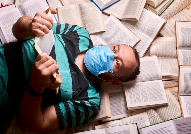 Uomo in maschera medica con molti libri di carta