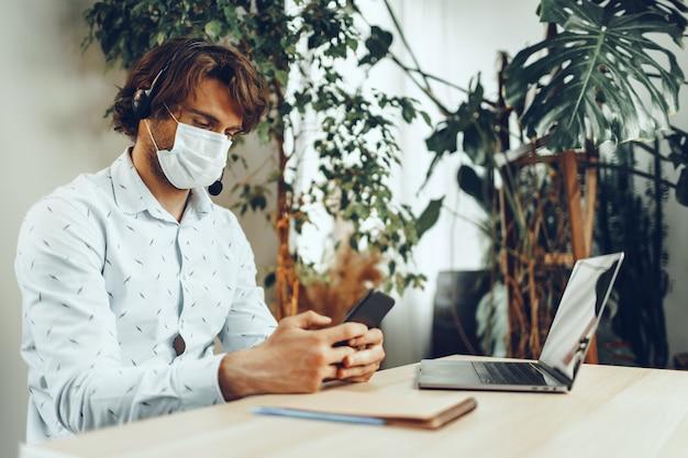 Uomo con maschera medica che lavora da casa durante la quarantena del coronavirus