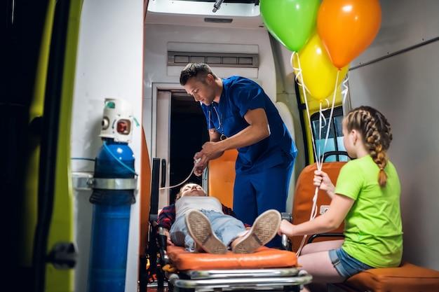 L'uomo in uniforme medica mette una maschera di ossigeno su una ragazza sdraiata su una barella, la sua sorellina sta guardando il dottore lavorare.