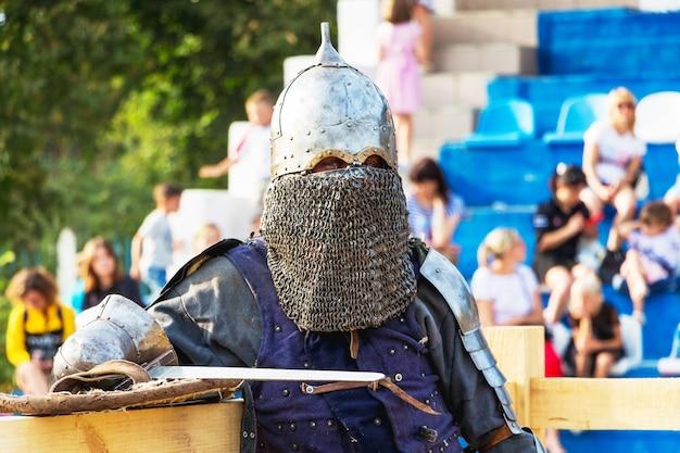 Un uomo in abiti da cavaliere medievale sulla tribuna di fondo con gli spettatori