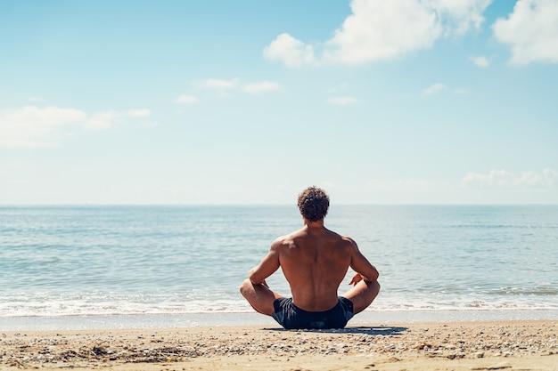 L'uomo medita sulla vista della spiaggia sabbiosa dal retro