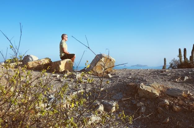 Uomo che medita sulla montagna vicino alla spiaggia