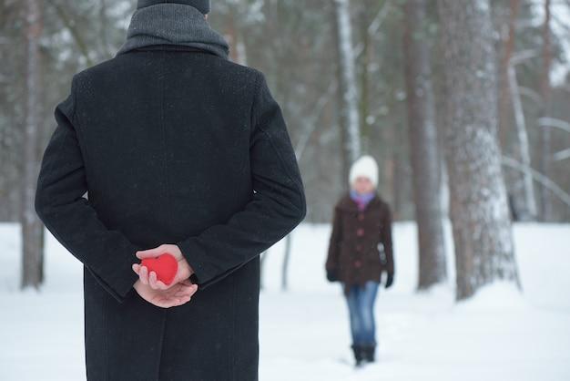 Un uomo incontra la sua donna e nasconde un cuore rosso dietro la schiena