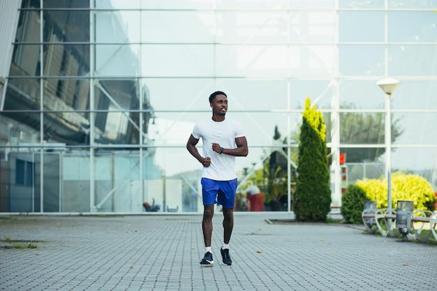 Uomo in corsa mattutina, giovane atleta afroamericano che corre vicino allo stadio