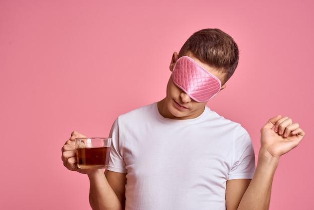 Uomo al mattino con una tazza di tè e una maschera per dormire