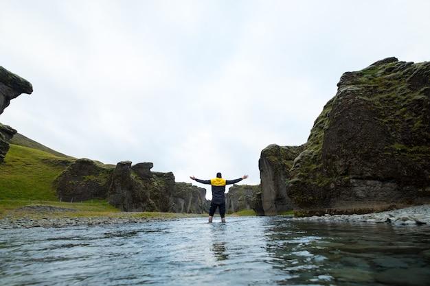 Uomo su una montagna islandese. il ragazzo, alza le mani al cielo. libertà e unità con la natura. sole che tramonta. turista all'aperto godendosi il paesaggio.