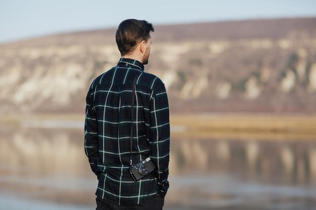 Uomo in montagna vicino al lago che tiene vecchia macchina fotografica