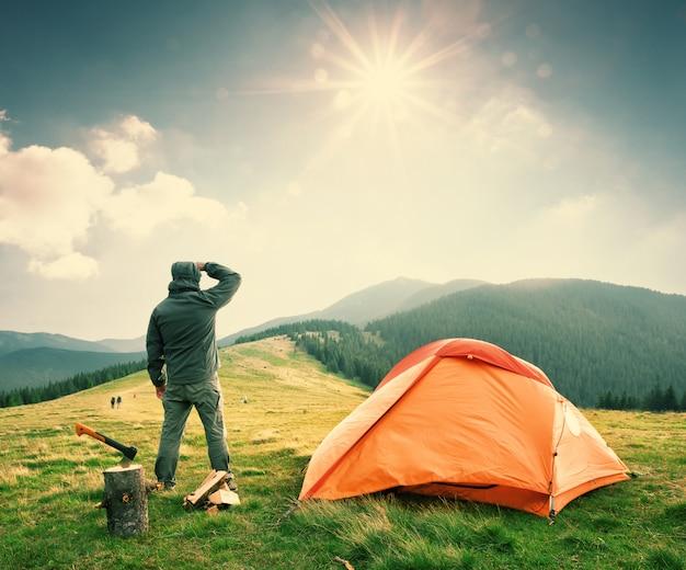 L'uomo sulla montagna vicino alla tenda arancione esamina la distanza