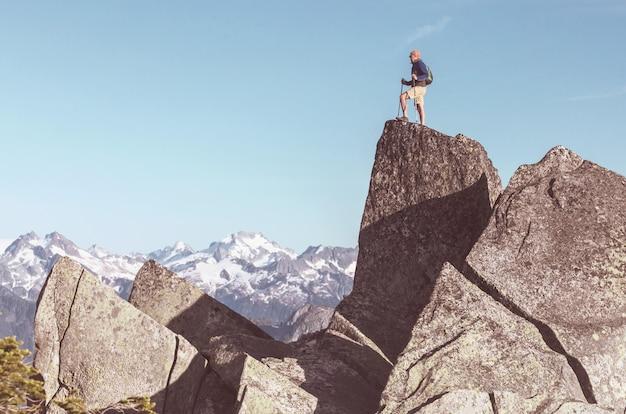 Uomo sulla scogliera di montagne. scena dell'escursionismo.