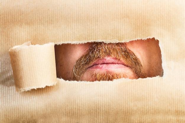 Una bocca di uomo attraverso un buco di una lacrima di carta marrone