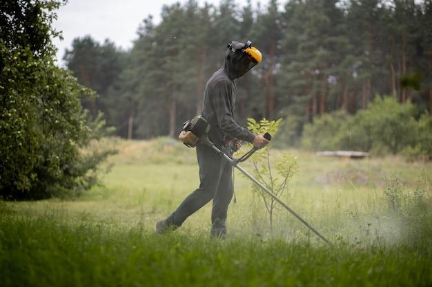 Uomo che falcia il prato nel suo giardino. giardiniere che taglia l'erba. stile di vita.
