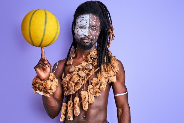 Uomo in abbigliamento nazionale autentico che tiene palla gialla in mano, andando a giocare a basket, con dipinti sul viso
