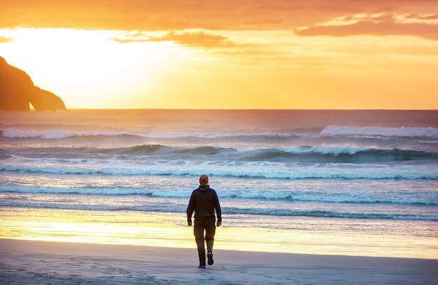 Uomo sulla spiaggia dell'oceano al tramonto. concetto di vacanza.