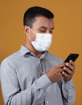 Uomo in camicia bianca che indossa la maschera con il cellulare nelle sue mani