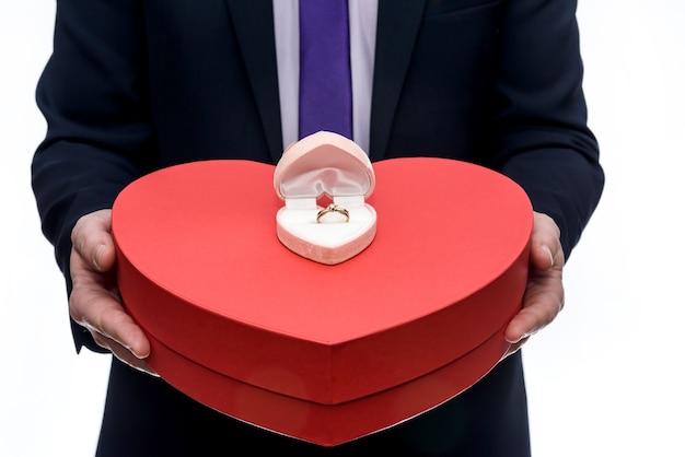 Uomo che offre anello d'oro e grande cuore rosso