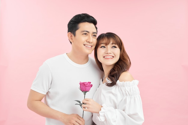 Uomo che offre una rosa alla sua ragazza su sfondo rosa